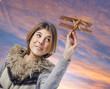 beautiful young woman playing with a wooden plane
