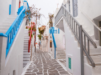 Fototapeta Mykonos town streetview with stairs and blue and grey and red banisters, Greece