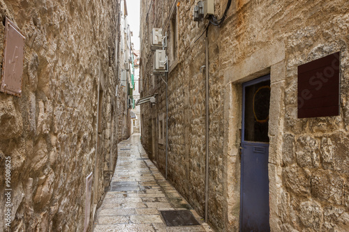 Poster Smal steegje Narrow, empty and wet alley or pedestrian street at the Old Town in Split, Croatia.