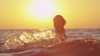 SLOW MOTION: Woman playing with sea water at beautiful sunset