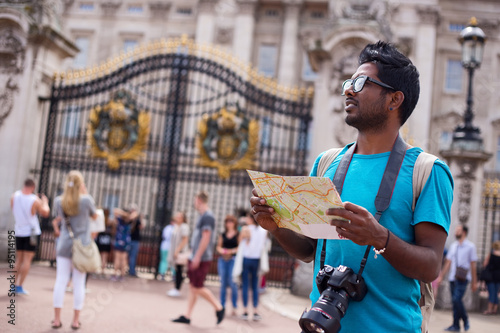 Indian tourist outside buckingham palace holding a map and his camera Canvas Print