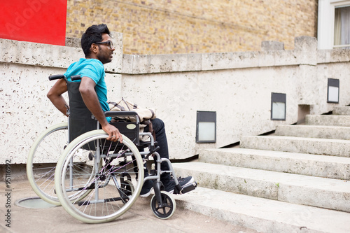 Photo  disabled man in a wheelchair waiting at the bottom of steps