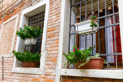 Papiers peints Jardin Decorated window with bouquet of flowers. Colorful houses island and landmark of Veneto region, Italy