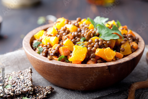 Photo sur Toile Plat cuisine Lentil with carrot and pumpkin ragout in a wooden bowl.