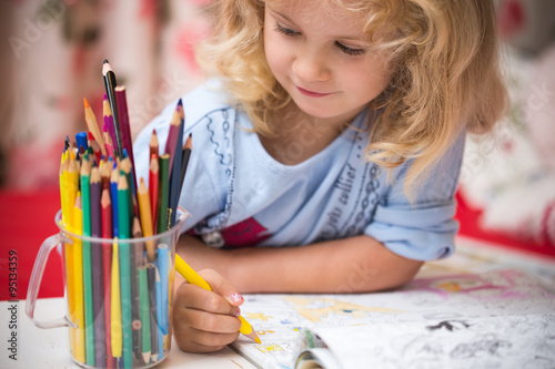 Valokuva  Portrait of child girl drawing with colorful pencils