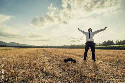 Fotografia  Successful businessman standing victoriously in the middle of fi