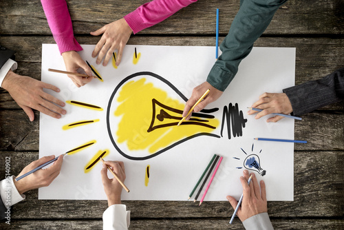 Stampe Six people, men and women, drawing bright yellow light bulb on a