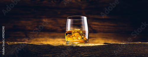 Foto op Plexiglas Alcohol Whiskey glass on the old wooden table