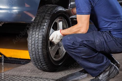 Fotomural Mecánico del neumático del coche de fijación Al taller de reparaciones