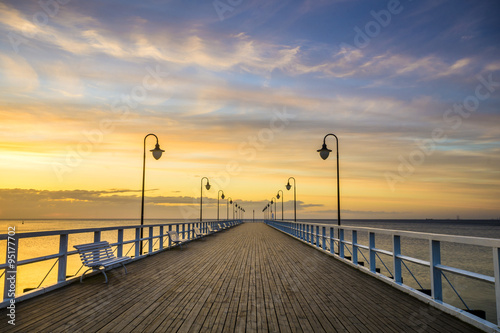 Fototapeta wooden pier by the sea lit by stylish lamps at night  obraz