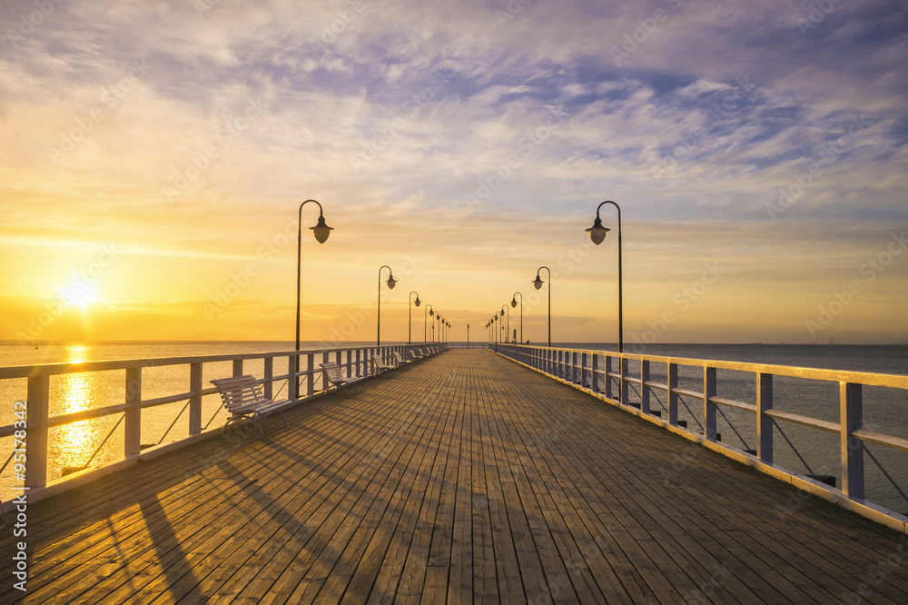 Fototapeta wooden pier by the sea lit by stylish lamps at night