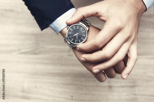 Fotografie, Obraz  mano di uomo con al polso orologio, con camicia e giacca elegante per lavoro