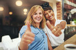 canvas print picture - Two happy young female friends giving a thumbs up