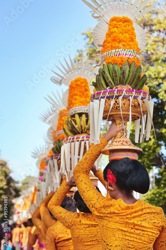 Canvas Prints Countryside Procession of beautiful Balinese women in traditional costumes - sarong, carry offering on heads for Hindu ceremony. Arts festival, culture of Bali island and Indonesia people, Asian travel background