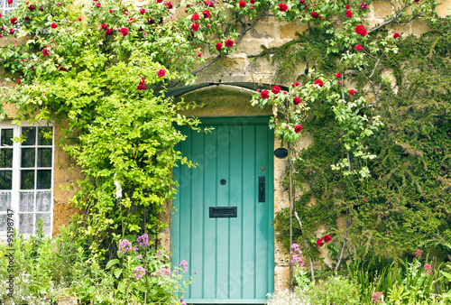 Photo  Green wooden doors in an old traditional English stone cottage surrounded by cli