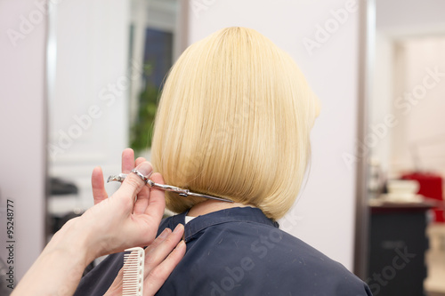 A hairdresser making haircut for a blonde female client