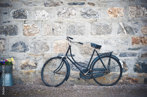 Deurstickers Fiets Old rusting bicycle leaning against a stone wall