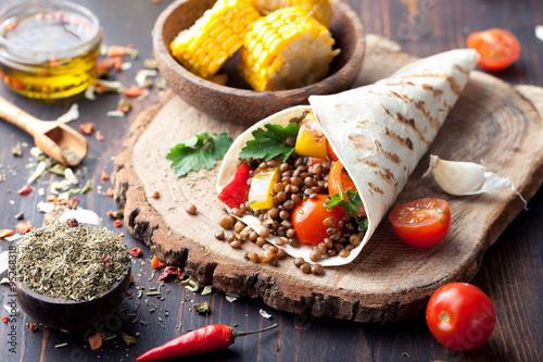 Obraz Vegan tortilla wrap, roll with grilled vegetabes, lentil, corn cob. - fototapety do salonu