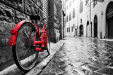 Fototapeta Alley - Retro vintage red bike on cobblestone street in the old town. Color in black and white