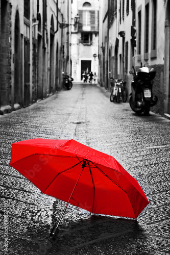 Fototapeta Red umbrella on cobblestone street in the old town Wind and rain