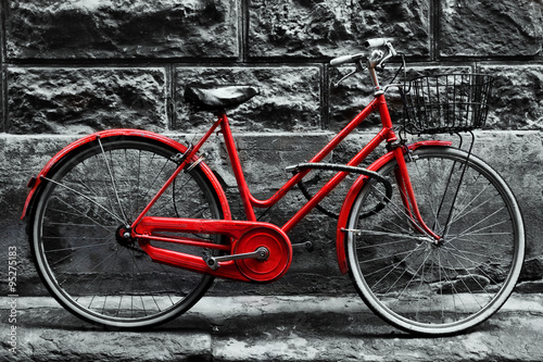 Fotobehang Fiets Retro vintage red bike on black and white wall.