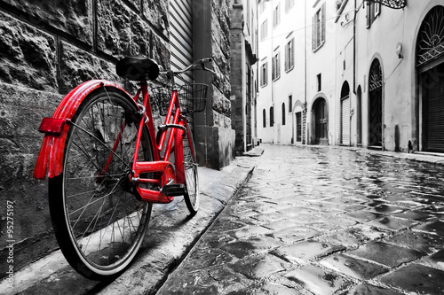 Photo Stands Bicycle Retro vintage red bike on cobblestone street in the old town. Color in black and white