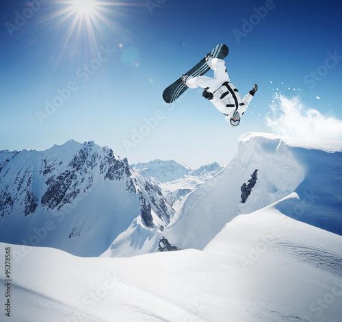 Snowboarder at jump inhigh mountains Wall mural