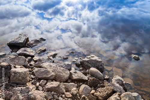 Fotografie, Obraz  Still lake coast, coastal stones and blue cloudy sky