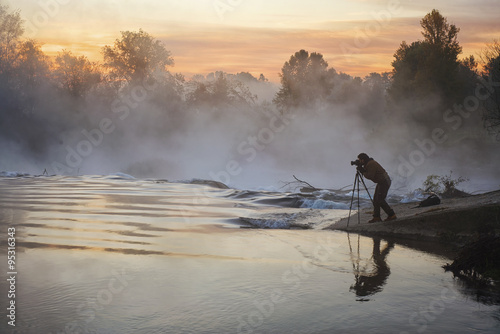 Poster Gris Photographer at dawn on the river in the mist