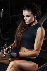 FototapetaSexy fitness brunette doing triceps exercises in the sport gym