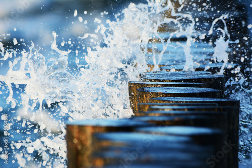 Valokuva  Wellen brechen sich an Buhnen im Meer
