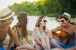 Teenagers having fun at the beach, are singing with guitare