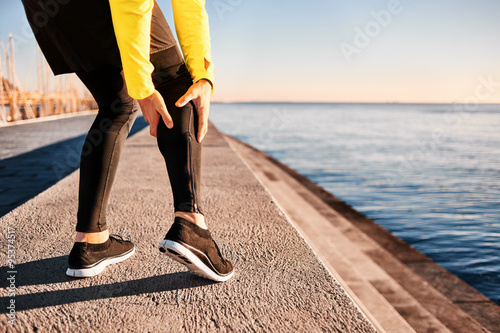 74e0770f95 Muscle injury - Athlete running clutching calf muscle after spraining it  while out jogging on the