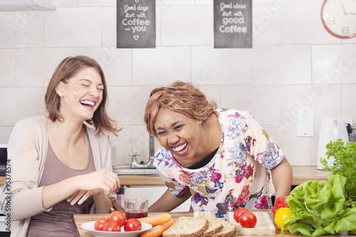 Poster de jardin Cuisine Happy friends cooking in kitchen