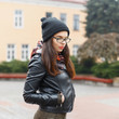 Pretty woman with glasses in warm hat and leather jacket