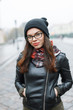 Beautiful woman in a knitted hat, sunglasses and leather jacket