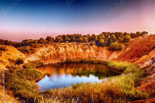 red soils around the lake in bauxite quarry Canvas Print