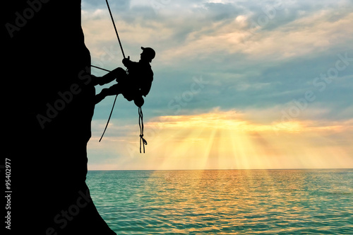 Photo Stands Mountaineering Silhouette climber climbing a mountain