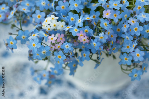 Fototapeta Forget-me-not flowers in a vase, close-up, fragment, blur.