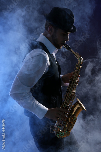 Elegant saxophonist plays jazz on dark background in blue smoke Fototapet