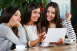 Beautiful friends look at something in tablet during drinking coffee in cafe