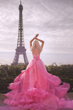 Beautiful Girl In A Pink Dress Near The Eiffel Tower In Paris