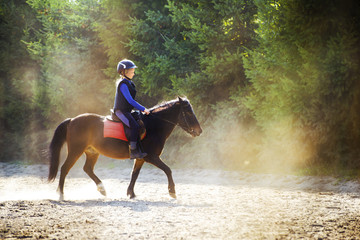 A young girl riding her pony during riding lesson, outside. Natural sun rays shining in dust during sunset.