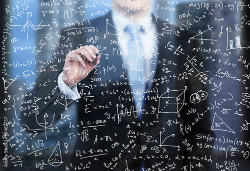 A business person is writing down math formulas on the glass screen in the evening modern panoramic office.