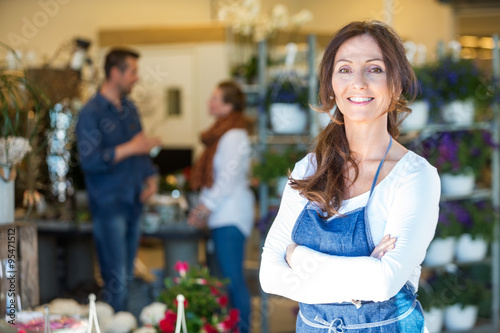 Valokuva  Portrait Of Smiling Florist At Flower Shop