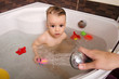 Toddler taking a bath. Little baby in a bathtub, mother's hand washing his hair with shampoo and soap. Kid playing with foam and water splashes. Clean kid after shower. Child hygiene.
