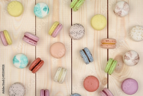 A lot of multicolored macarons on wooden background