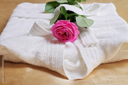 Fotografie, Obraz  Stack of white  and soft hotel towels and bathrobe decorated with rose flower