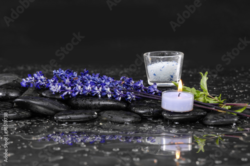 Photo  bunch of lavender flower with candle ,salt in glass on wet black stone