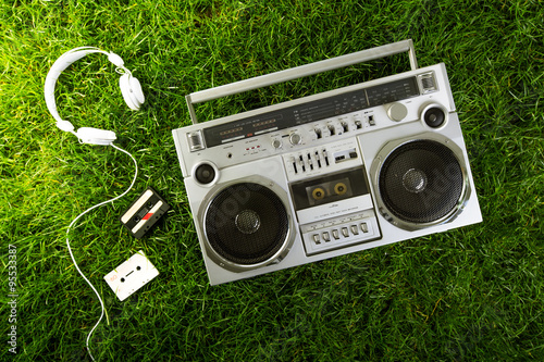 Photo  Retro-styled silver boom box, earphones and audio cassettes over